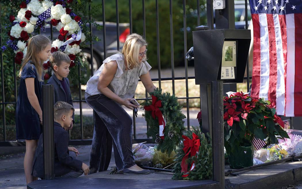 Tiffany Utterson, derecha, y sus hijos, de izquierda a derecha, Ella, 11, Ian, 10 y Owen, 8, colocan una corona fuera de la entrada de la comunidad cerrada a la casa de George H.W. Bush domingo, 2 ...