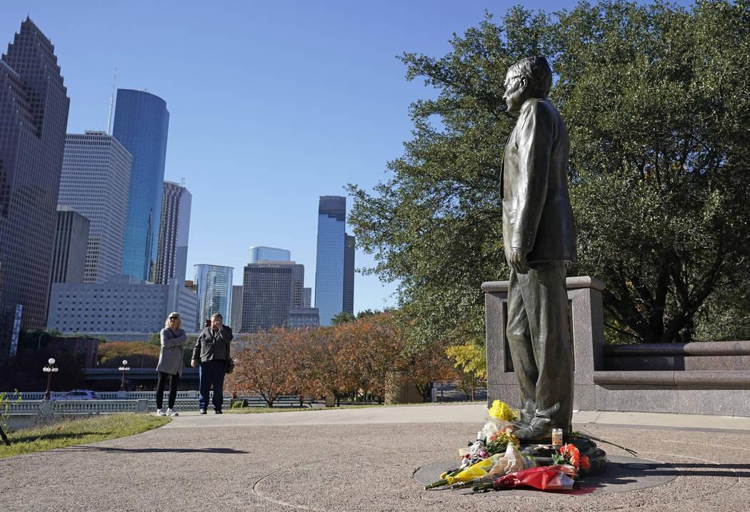 Deitz Kracker, a la izquierda, y Marg Frazier visitan una estatua del ex presidente George H.W. Bush en el centro de Houston, domingo 2 de diciembre de 2018. Bush murió el viernes por la noche en ...