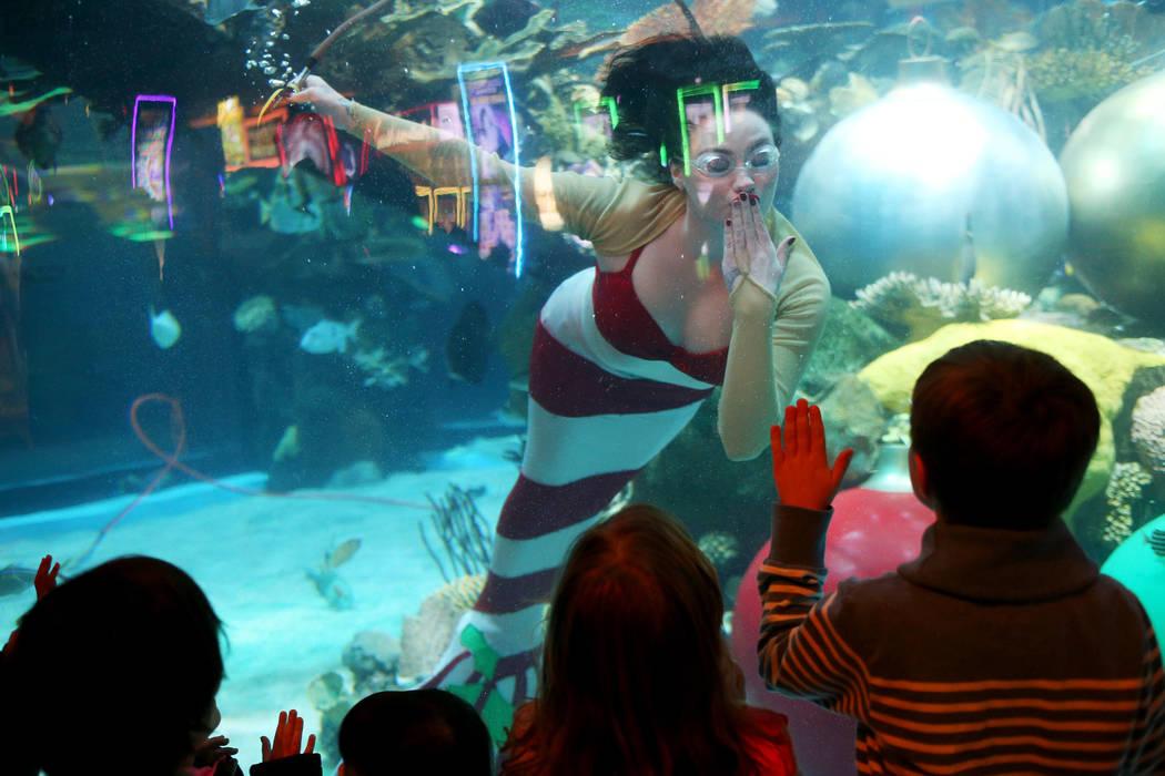 La sirena navideña le da un beso a Matvay Sokolov, de 6 años, en el hotel y casino Silverton en Las Vegas, el domingo 2 de diciembre de 2018. Ella y Santa están en el acuario todos los sábados ...