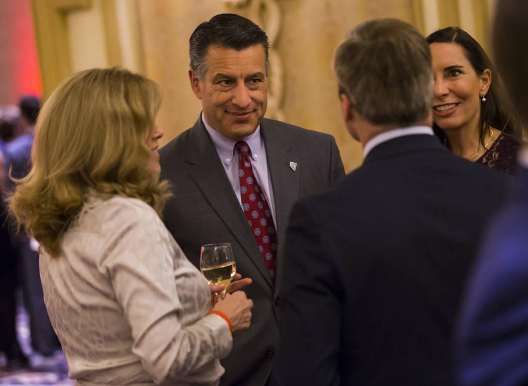 El gobernador Brian Sandoval habla junto a su esposa Lauralyn McCarthy mientras se mezcla con los invitados durante la Gala de la Ley de la UNLV en Bellagio en Las Vegas el sábado 1 de diciembre ...