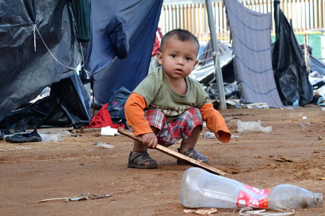 Un niño juega en el lodo en un campamento de migrantes en Tijuana. (Doug Kari/Especial para el Las Vegas Review-Journal)