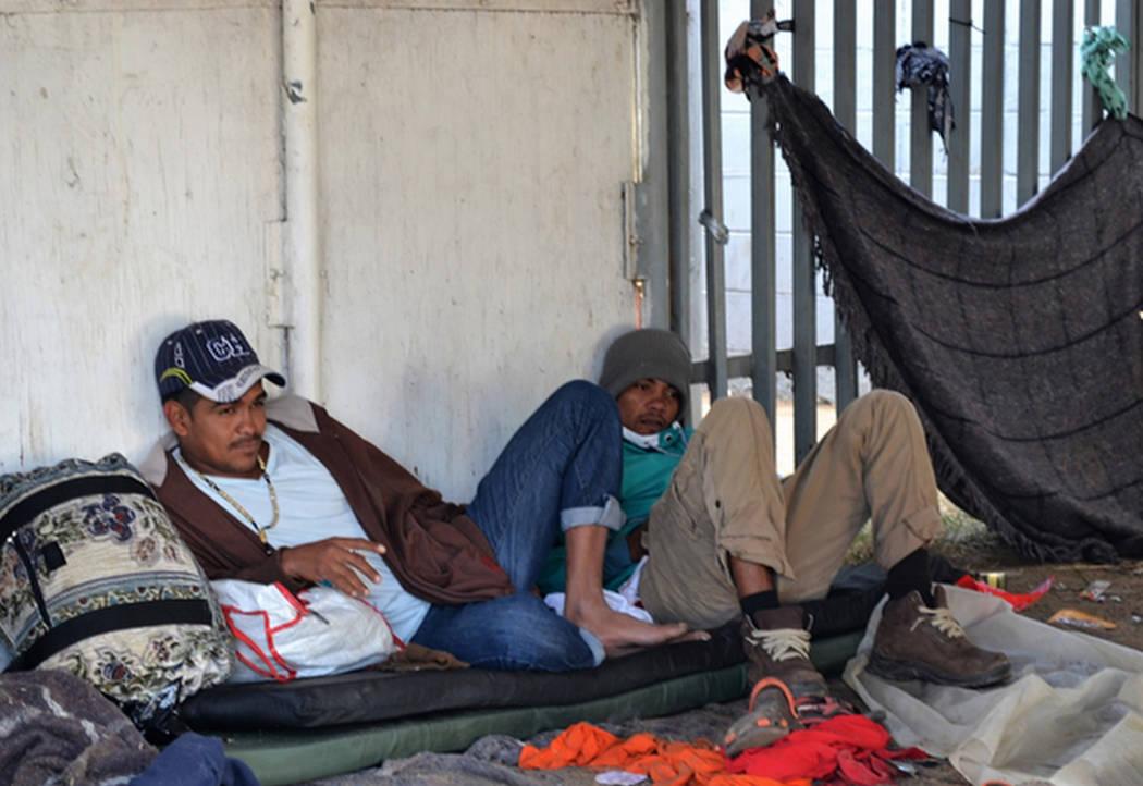 Hombres migrantes el viernes, después de una larga noche de lluvia. (Doug Kari/Especial para el Las Vegas Review-Journal)