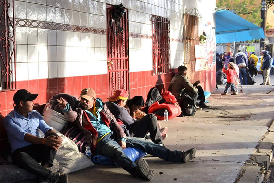 Los hombres esperan para ser llevados en autobús al refugio para migrantes El Barretal en Tijuana. (Doug Kari/Especial para el Las Vegas Review-Journal)