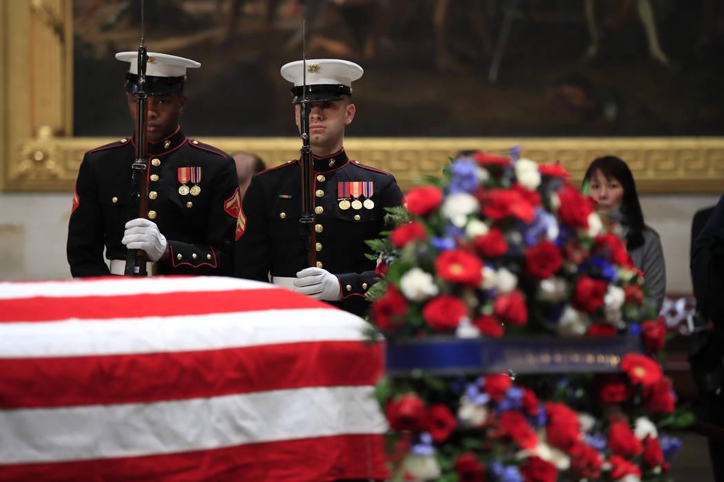 La guardia de honor del Cuerpo de Marines de los Estados Unidos ejecuta un saludo de rifle durante el cambio de guardia en la Rotonda del Capitolio, donde se vela al ex presidente George H.W. Bush ...