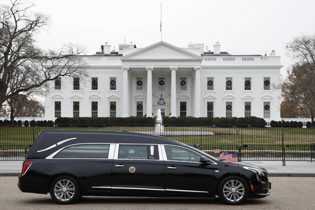 El coche fúnebre con el ataúd cubierto por la bandera del ex presidente George H.W. Bush pasa por la Casa Blanca desde el Capitolio, y se dirige a un funeral en la Catedral Nacional, el miércol ...
