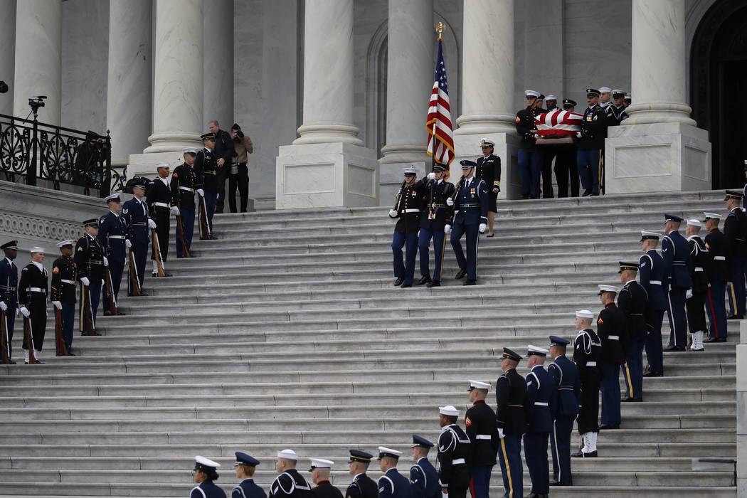 El ataúd abanderado del ex presidente George H.W. Bush es transportado por una guardia de honor militar de servicios conjuntos del Capitolio de los EE.UU., El miércoles 5 de diciembre de 2018, e ...