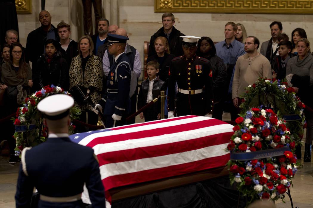 Los visitantes presentan sus respetos al ataúd abanderado del ex presidente George H.W. Bush, mientras se encuentra en el estado en el Capitol Rotunda en Washington, miércoles, 5 de diciembre de ...