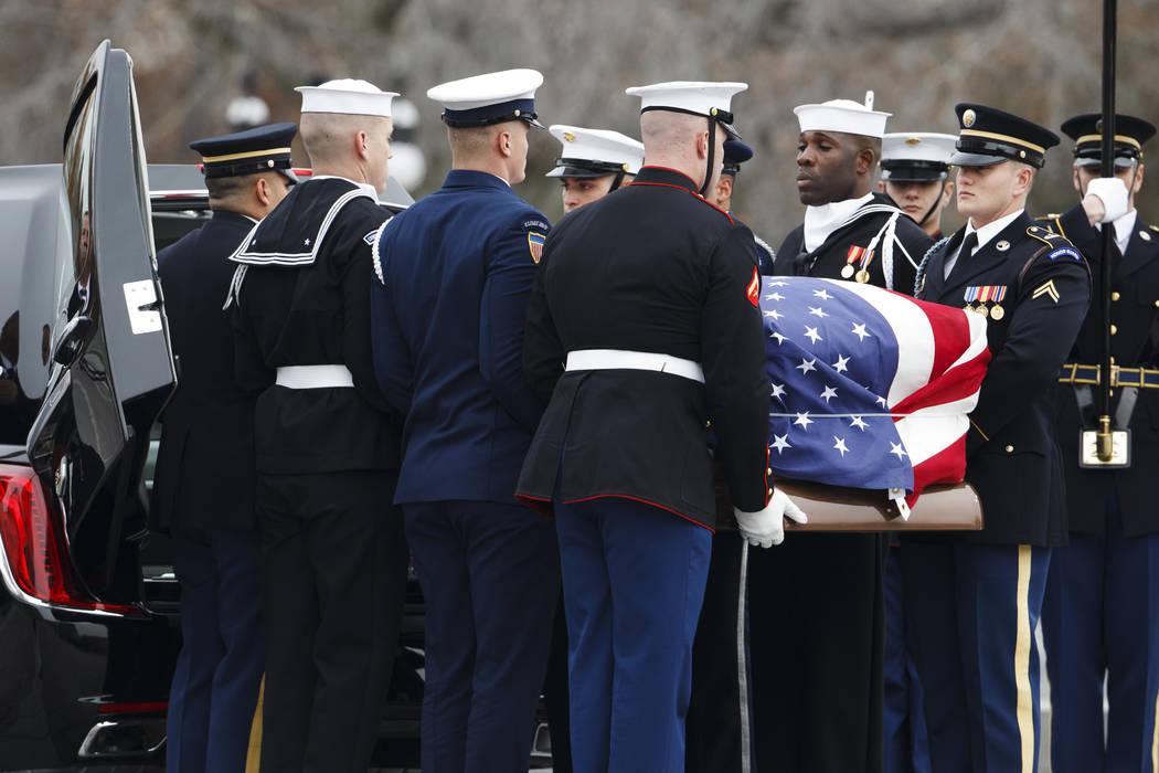 El ataúd abanderado del ex presidente George H.W. Bush es llevado a un coche fúnebre por una guardia de honor militar de servicios conjuntos del Capitolio de los EE.UU., El miércoles 5 de dicie ...