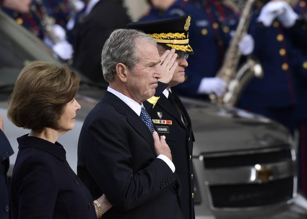 El ex presidente George W. Bush y su esposa, Laura Bush, ven como el ataúd del ex presidente George H.W. Bush llega a la Catedral Nacional, el miércoles 5 de diciembre de 2018, en Washington, pa ...