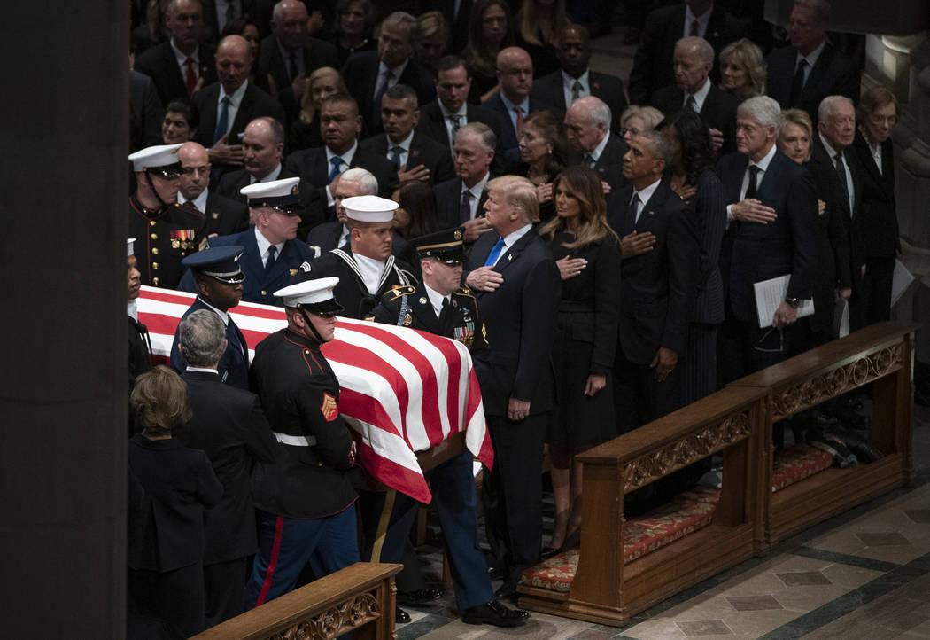 El ataúd abanderado del ex presidente George H.W. Bush es llevado por una guardia de honor militar que pasa por el ex presidente George W. Bush y su esposa Laura Bush, al presidente Donald Trump, ...