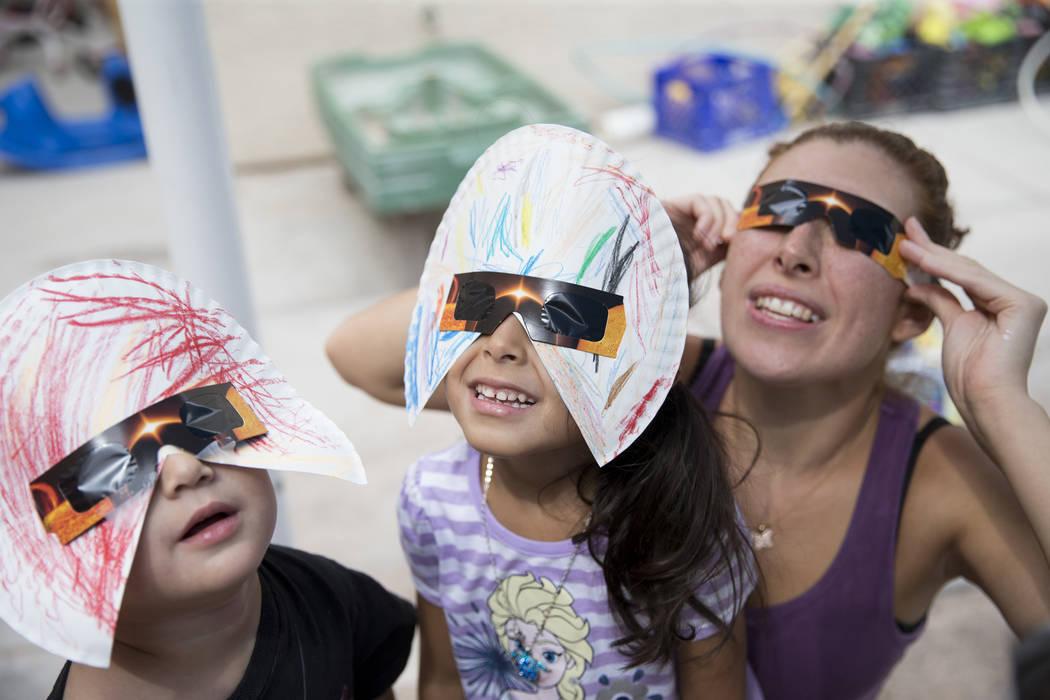 Joseph Hernández-Bernabei, de 3 años, desde la izquierda, Gisele Oseguera, 3, y su madre, Mónica Cuevas, observan el eclipse solar en la guardería Keeping Youth Educated en Las Vegas, el lunes ...