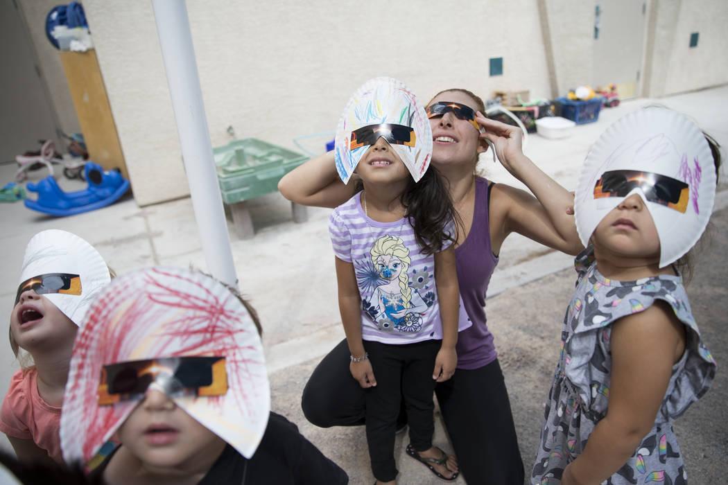 Amilya Durnen, de 3, desde la izquierda, Joseph Hernández-Bernabei, de 3, con su hermana gemela Sofía, a la derecha, y Mónica Cuevas con su hija Gisele Oseguera, de 3, ven el eclipse solar en l ...