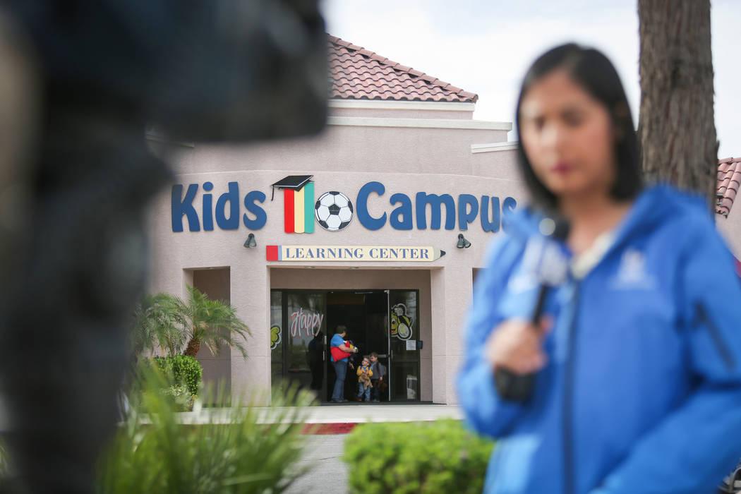 Una familia sale de la guardería Kids Campus mientras un reportero de televisión entrega un informe en vivo en North Las Vegas el viernes 6 de mayo de 2016. El jueves, la policía dice que Travi ...
