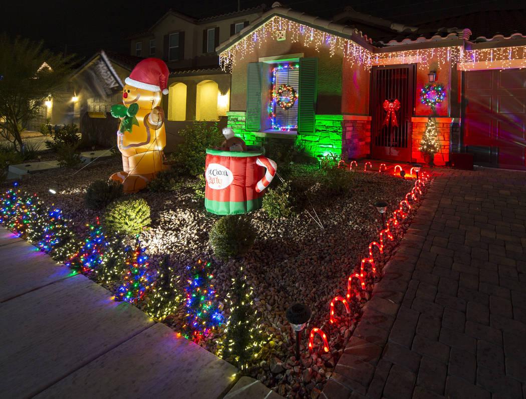 Los residentes de Henderson, Becky y GG Misa, posan afuera de su casa decorada con una exhibición de luces de Navidad que está sincronizada con la música de entrada de los Caballeros Dorados ub ...