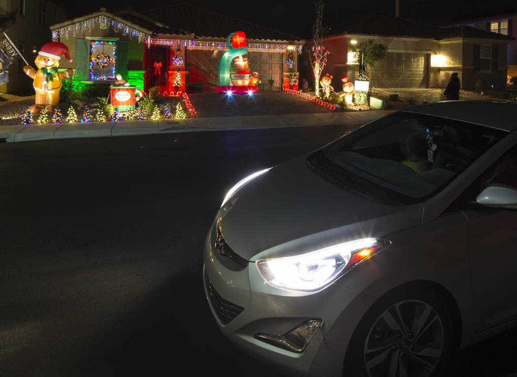 Una familia en un automóvil observa la exhibición de luces navideñas de Becky y GG Misa que está sincronizada con la música de entrada de los Caballeros Dorados ubicada en 730 Bollons Island ...