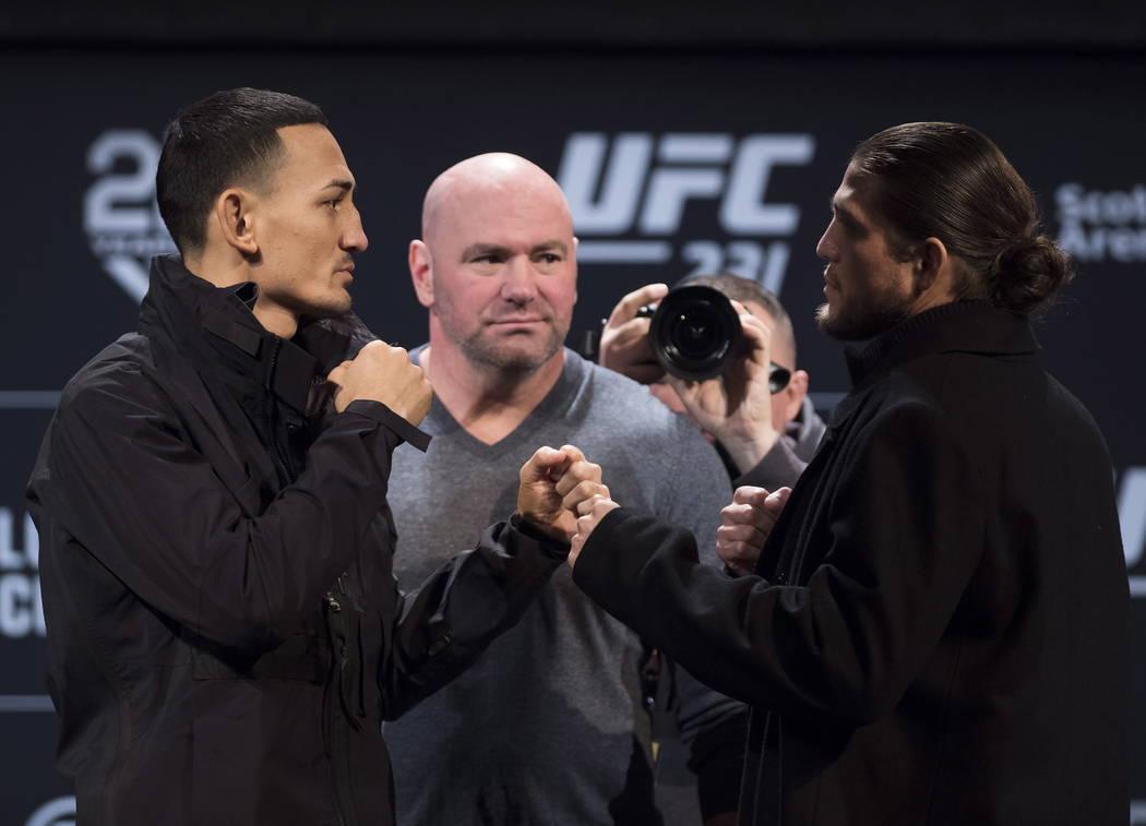 El presidente de la UFC, Dana White, centro, mira al campeón de peso pluma de la UFC Max Holloway, a la izquierda, y al luchador de peso pluma,Brian Ortega, durante una conferencia de prensa, el ...
