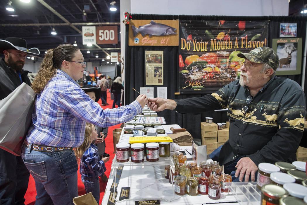 Tadd Mick, a la derecha, le da a Michele Davis una muestra de gelatina de pimienta en Micks Peppouri durante el Cowboy Christmas en el Centro de Convenciones de Las Vegas el jueves 6 de diciembre ...