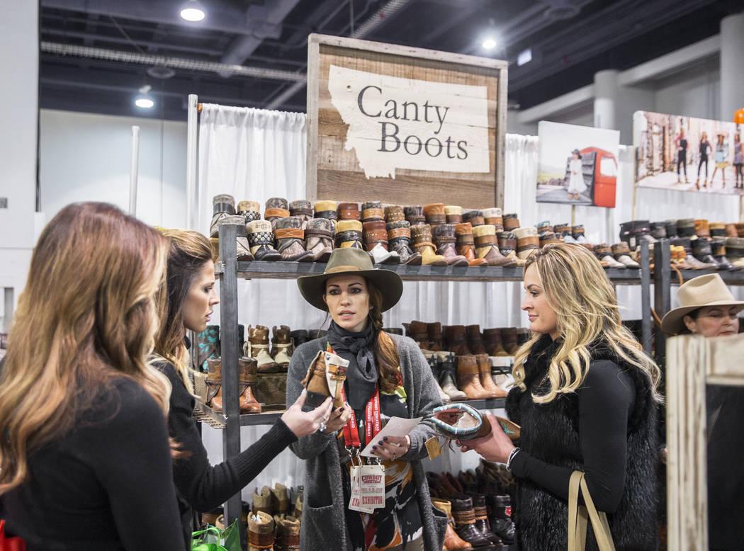 Nikki Edmundson, en medio, ayuda a los clientes de Canty Boots, con sede en Montana, durante Cowboy Christmas en el Centro de Convenciones de Las Vegas el jueves 6 de diciembre de 2018, en Las Veg ...