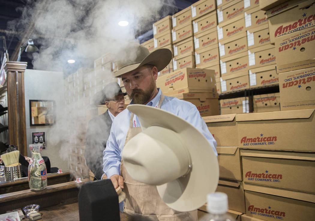 Tye Chesser, un representante de ventas de American Hat Company, ayuda a un cliente durante Cowboy Christmas en el Centro de Convenciones de Las Vegas el jueves 6 de diciembre de 2018, en Las Vega ...