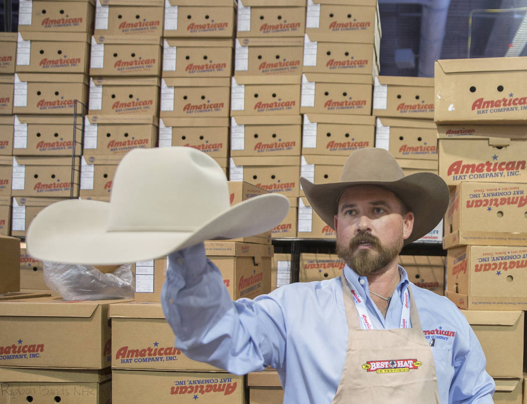 Tye Chesser, a la derecha, un representante de ventas de American Hat Company, ayuda a un cliente durante Cowboy Christmas en el Centro de Convenciones de Las Vegas el jueves 6 de diciembre de 201 ...