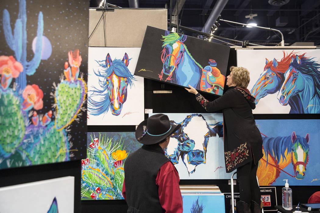 El artista Lyndon Gaither, a la izquierda, de Dallas, Texas, y su esposa Bárbara cuelgan una pintura en Contemporary Western Art en Cowboy Christmas en el Centro de Convenciones de Las Vegas el j ...