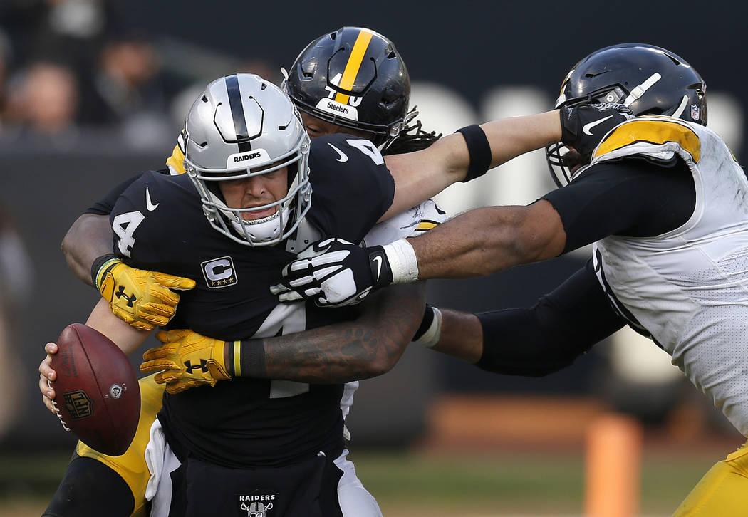 El mariscal de campo de los Raiders de Oakland, Derek Carr (4), es saqueado por el linebacker externo Bud Dupree de los Pittsburgh Steelers, detrás, mientras el alero defensivo Cameron Heyward, d ...