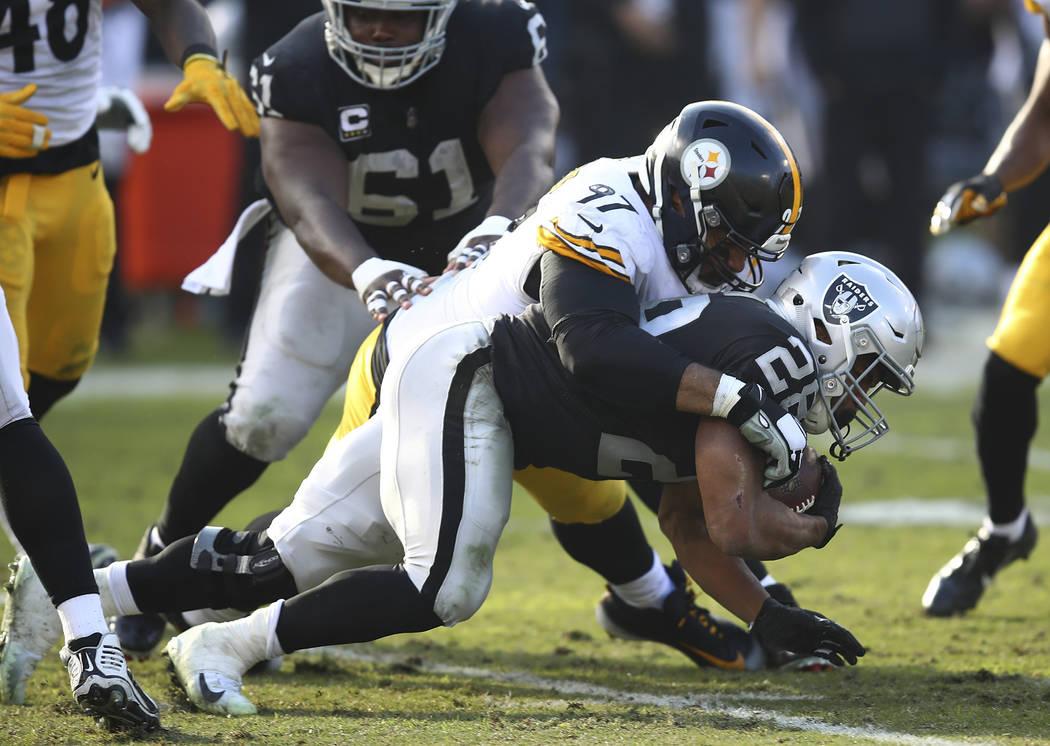 El alero defensivo de los Pittsburgh Steelers, Cameron Heyward (97), se enfrenta al corredor de los Raiders de Oakland, Doug Martin (28), durante la primera mitad de un partido de fútbol american ...