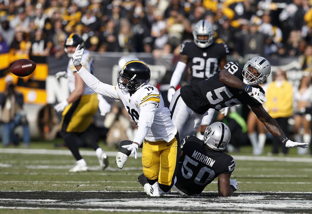 El receptor abierto de los Pittsburgh Steelers, JuJu Smith-Schuster (19), no pudo atrapar un pase frente al linebacker de los Oakland Raiders, Tahir Whitehead (59), y al linebacker Nicholas Morrow ...