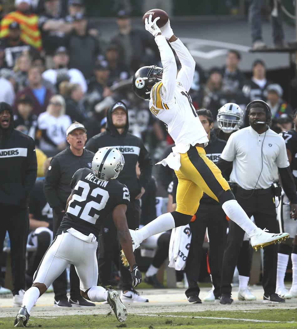 El receptor abierto de los Pittsburgh Steelers, JuJu Smith-Schuster, arriba, atrapa un pase sobre el corredor defensivo de los Raiders de Oakland, Rashaan Melvin (22), durante la primera mitad de ...