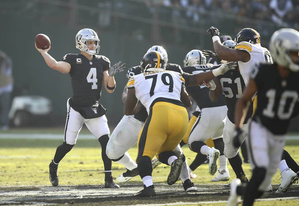 El mariscal de campo de los Oakland Raiders, Derek Carr (4), pasa ante los Pittsburgh Steelers durante la primera mitad de un partido de fútbol de la NFL en Oakland, California, el domingo 9 de d ...