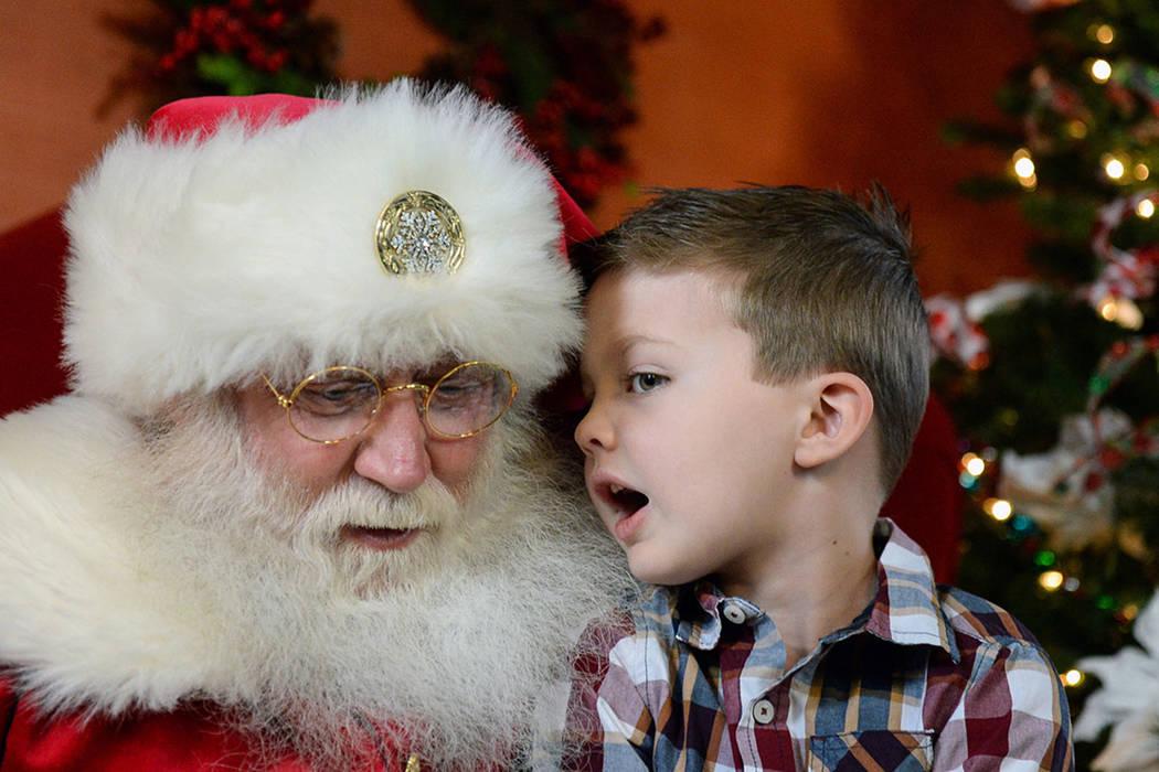 Maverick Willis, de 5 años, de Henderson, le susurra al oído a John Jones, disfrazado de Papá Noel, mientras le dice lo que quiere para Navidad en el distrito de Green Valley Ranch en Henderson ...