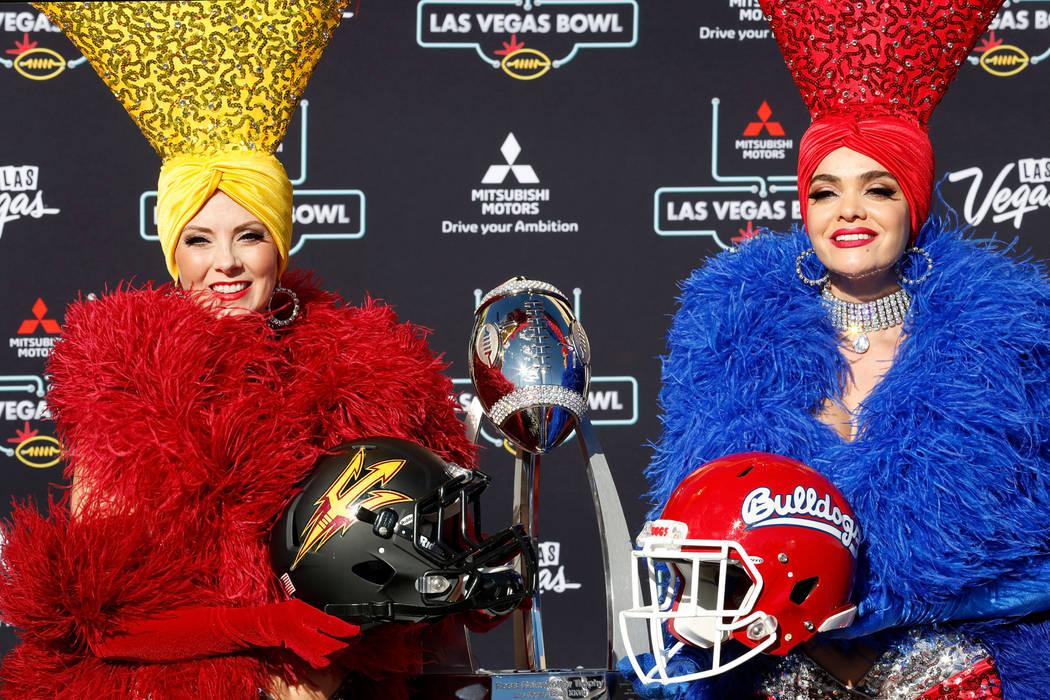 Las showgirls Jennifer Autry, a la izquierda, con un casco de fútbol americano de Arizona State y Porsha Revesz con un casco de Fresno State, posan para una foto durante una conferencia de prensa ...