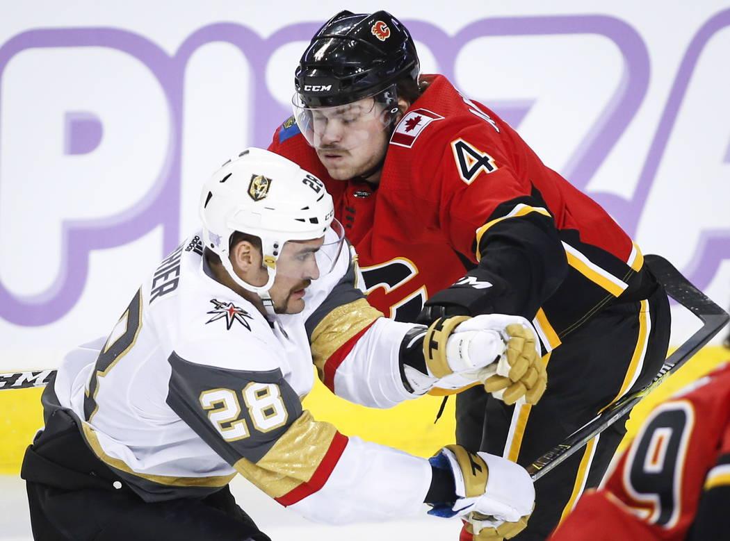 William Carrier de los Vegas Golden Knights, a la izquierda, taclea a Rasmus Andersson, de Suecia, de Calgary Flames, durante el primer tiempo de un juego de hockey de la NHL en Calgary, Alberta, ...