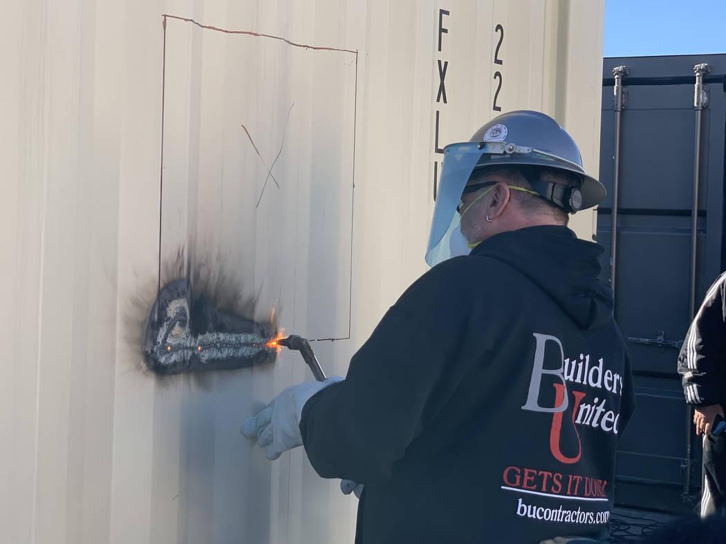 Rick Rainy, de Builders United, que simboliza un corte de listón, utiliza un soplete de soldadura para iniciar el primer corte en un nuevo contenedor para hogar en Veterans Village II, 50 N. 21st ...