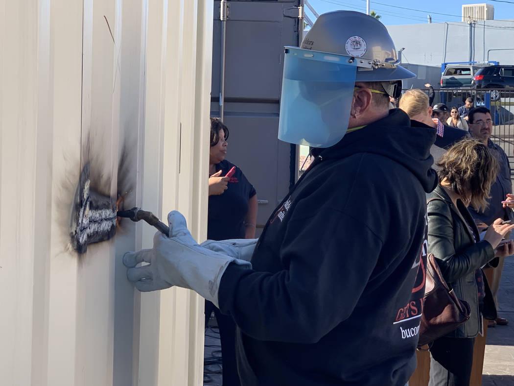 Rick Rainy, de Builders United, simbolizando un corte de listón, utilizando una antorcha de soldadura para comenzar el primer corte en un nuevo contenedor para hogar en Veterans Village II, 50 N. ...