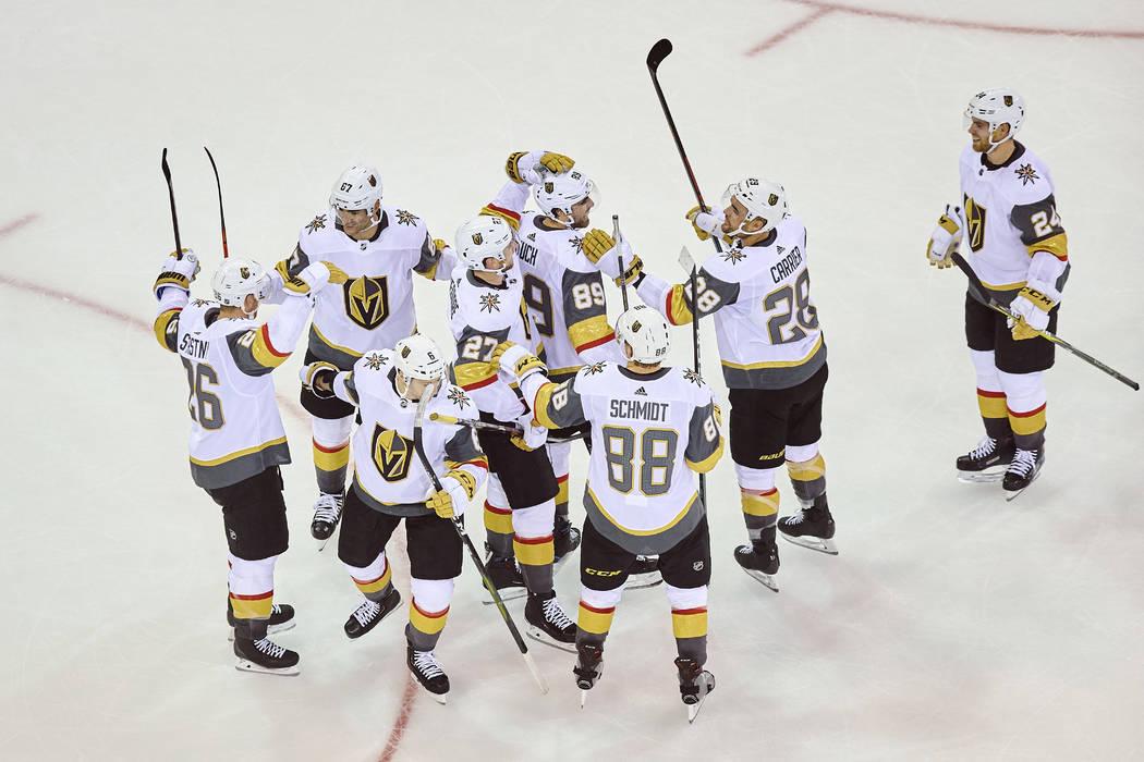 Alex Tuch (89), líder de Vegas Golden Knights, celebra con sus compañeros de equipo después de marcar un gol durante el tiempo extra de un juego de hockey de la NHL contra los New York Rangers, ...