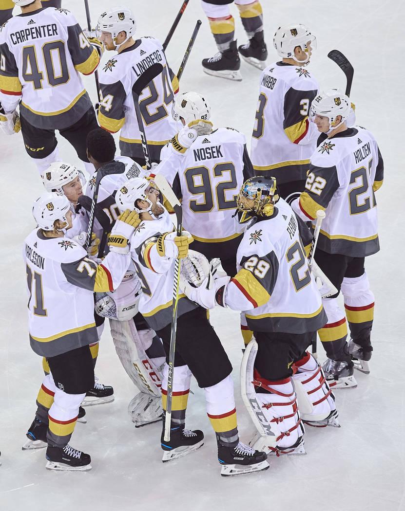 Alex Tuch de los Vegas Golden Knights, en el centro inferior, celebra con sus compañeros de equipo luego de marcar un gol durante el tiempo extra de un juego de hockey de la NHL contra los Ranger ...