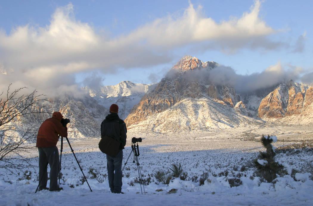 Los fotógrafos se reúnen en el Red Rock Overlook en la ruta estatal 159 para capturar imágenes de las montañas cubiertas de nieve del Área de Conservación Nacional Red Rock Canyon en la madr ...
