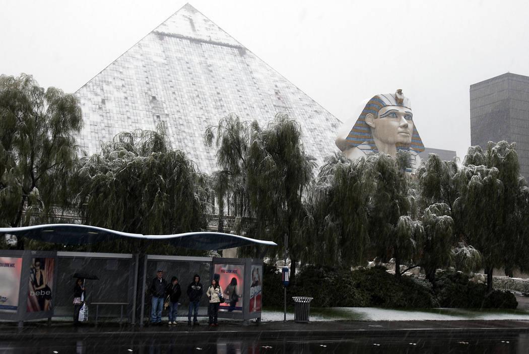 La gente espera un autobús mientras la nieve que cae cubre el Luxor en el Strip de Las Vegas, el 17 de diciembre de 2008. (John Gurzinski / Las Vegas Review-Journal)