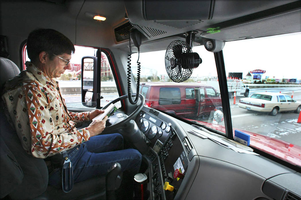 El conductor de camiones de tractores y remolques Gary Mott se pone al día con su lectura en la carretera interestatal 15 en Primm el 18 de diciembre de 2008, después de que la carretera interes ...