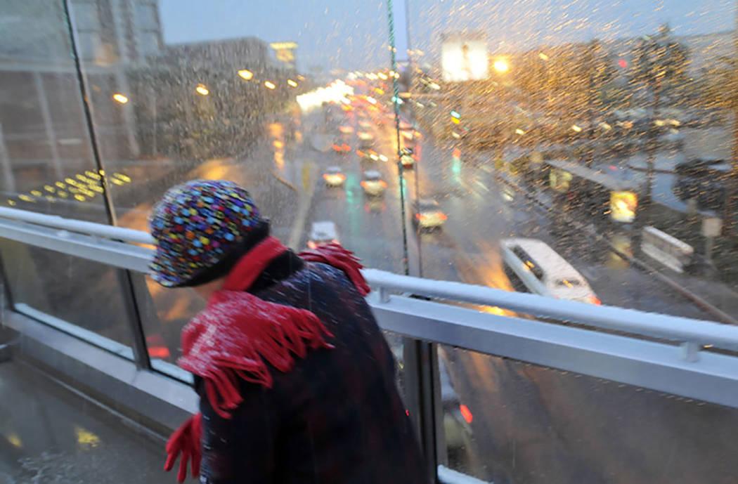 Una mujer pasando por la lluvia helada y la nieve mientras cruza uno de los puentes peatonales a lo largo del Strip de Las Vegas el 17 de diciembre de 2008. (Las Vegas Review-Journal)
