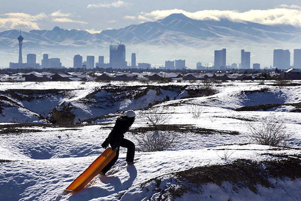 Con el horizonte de Las Vegas al fondo, Kymberlee Nguyen se dirige a la cima de una colina mientras se desliza en una región desértica cerca de North Durango Road el 18 de diciembre de 2008. (La ...