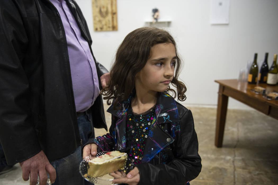Beatrix Wiersma, de 8 años, de Las Vegas, recibe un pedazo de pastel que se sirve en una exhibición en Core Contemporary Gallery en Las Vegas, el jueves 6 de diciembre de 2018. Caroline Brehman ...