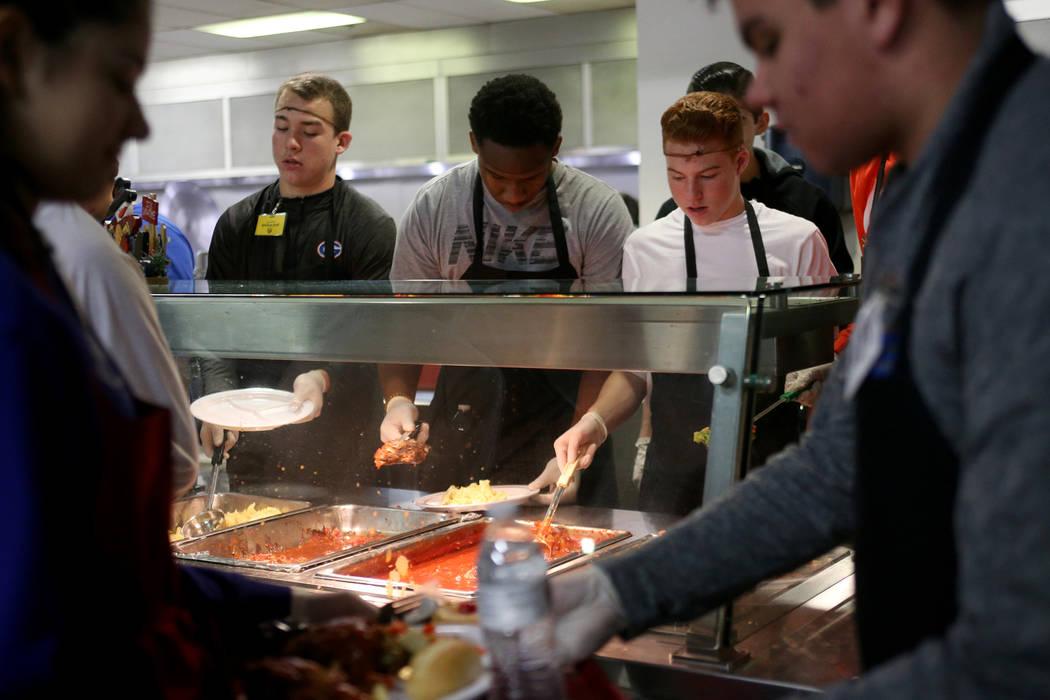 Michael Frailey, de 15 años, a la izquierda, Camden Miller, de 15, y Cameron Gray, de 14, todos estudiantes del equipo de fútbol Bishop Gorman High School, sirven comida en la cena de Navidad pa ...