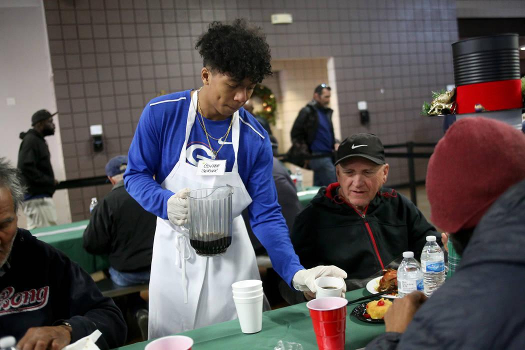 Jovani Hawkins, de 17 años, sirve café a los invitados en la cena de Navidad patrocinada por la Fundación Frank y Victoria Fertitta, en Catholic Charities of Southern Nevada en Las Vegas, el do ...