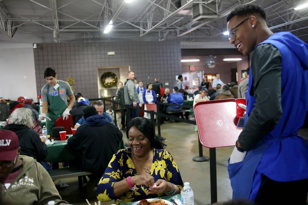 Donovan Smith, de 17 años, se ríe con Laurice Adams en la cena de Navidad patrocinada por la Fundación Frank y Victoria Fertitta, en Catholic Charities del Sur de Nevada en Las Vegas, el doming ...