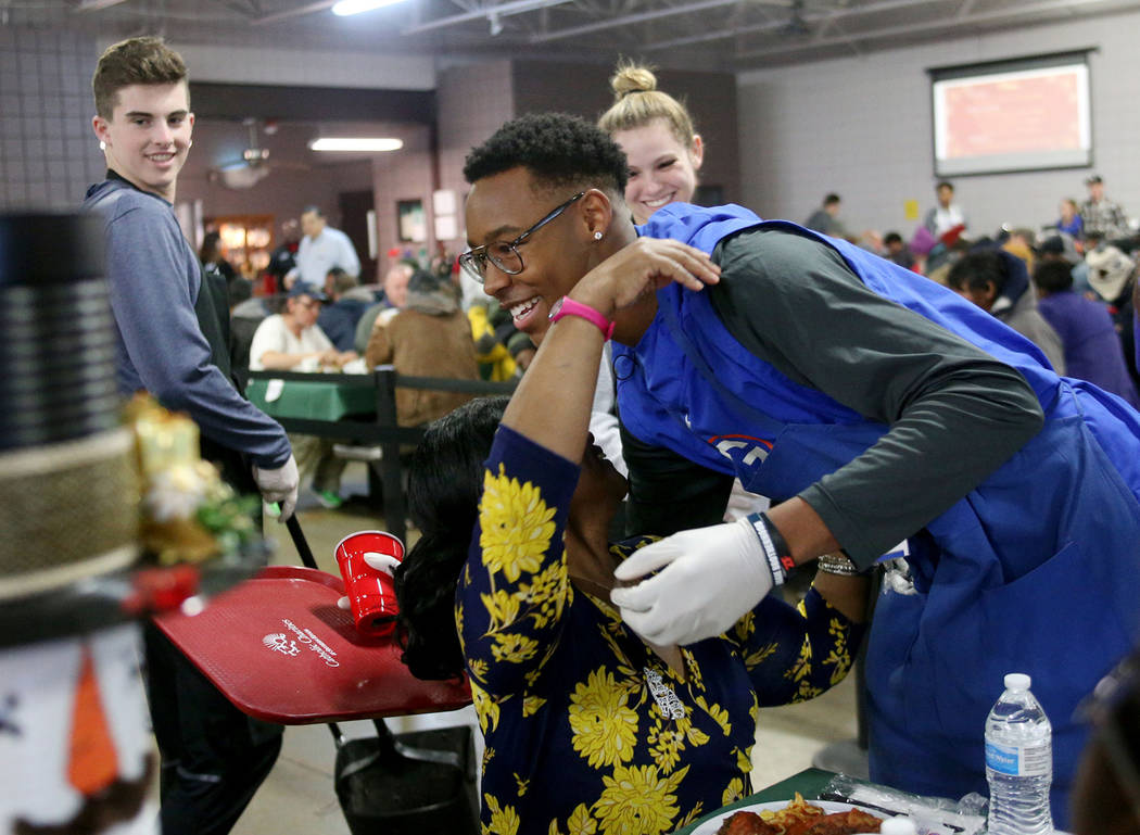 El voluntario Donovan Smith, de 17 años, miembro del equipo de fútbol de Bishop Gorman, abraza a Laurice Adams, invitada, en la cena de Navidad patrocinada por la Fundación Frank y Victoria Fer ...