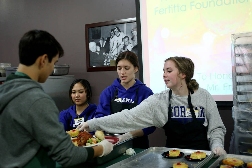 Kelly Hashiro, 17, desde la izquierda, Keira Fincher, 15, y Haley Taylor, 17, sirven postre y pan en la cena de Navidad patrocinada por la Fundación Frank y Victoria Fertitta, en Catholic Chariti ...