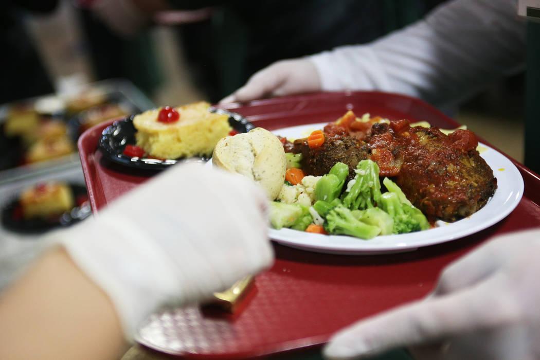 Un plato de pollo, cacciatore, pastas de huevo con mantequilla, medley de ajo california, rollo de cena y pastel de piña en la cena navideña patrocinada por la Fundación Frank y Victoria Fertit ...