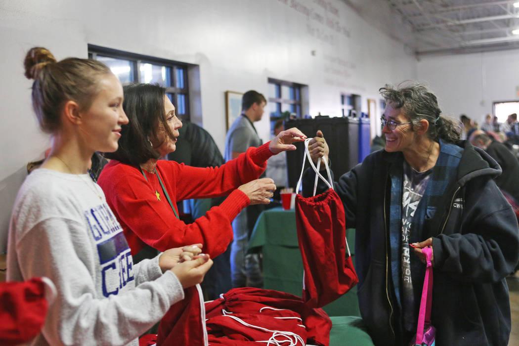 Sandee Tiberti le entrega una bolsa de regalo de artículos de tocador, agua y calcetines a Corey Gunter en la comida de Navidad patrocinada por la Fundación Frank y Victoria Fertitta, en Catholi ...